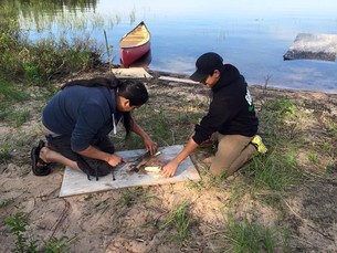 Fort Chipewyan student learning how to fillet a fish